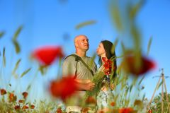 A man and a woman in a field of poppies stock photo