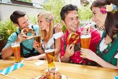 Men and women flirting in bavarian. Beer garden in summer royalty free stock image