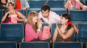 Men and Women Flirting in Theater. Flirtacious men with 2 young women in theater stock photo