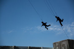 Men and women flying in sky with safety rope. Royalty Free Stock Photos