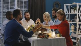 Group of friends praying on Thanksgiving day celebration. Men and women giving worship before starting delicious meal at table having Thanksgiving holiday stock image