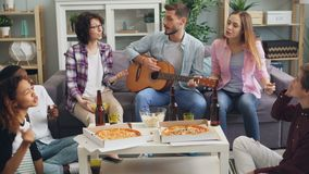 Men and women friends playing the guitar and singing together at party in house stock footage