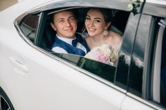 A man and a woman are hugging in the back seat of the car. Portrait of lovers looking at the open window of the car and stock image