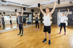 Men And Women Lifting Barbells In Fitness Club Royalty Free Stock Photo