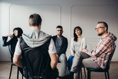 Men and women listening about teenager`s anxiety problems during group therapy stock images