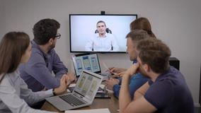 Men and women are listening to boss by video call in office room of company of development of mobile apps