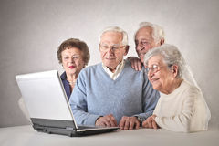 Men and women looking at a laptop stock image