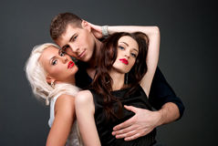 Men and women love. Hot love story. Handsome men and two women passionately embraces. A loving relationship between a men and two women. Love, passion, betrayal Royalty Free Stock Photos