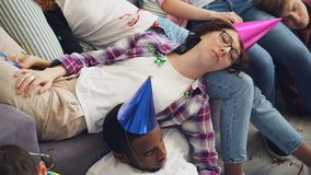 Men and women in party hat sleeping on couch and floor after celebration at home stock footage