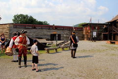 Men and women in period dress, showing visitors how to fire a musket,Fort William Henry,New York,2015 Royalty Free Stock Photography