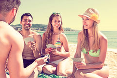 Men and women playing cards. Two men and two women playing card games on a beach on a sunny summer day stock image