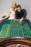 Men with women playing roulette at the casino. Royalty Free Stock Photography