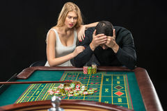 Men with women playing roulette at the casino. Royalty Free Stock Image