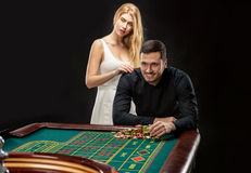 Men with women playing roulette at the casino. Player follows the risky game Royalty Free Stock Images