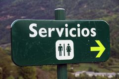 Men and women public restroom and toilet signs with direction arrow symbol. In spain Royalty Free Stock Photo