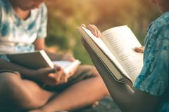 Men and women read books in quiet nature. stock photo