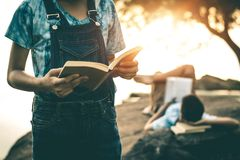 Men and women read books in quiet nature. stock photography
