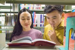 Man and woman read and talk open book at bookshelf Royalty Free Stock Photography