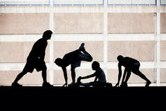 Men and women runners stretching. Royalty Free Stock Images