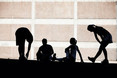 Men and women runners stretching. royalty free stock image