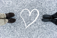 Men and women`s boots standing at abstract heart symbol on asphalt covered gritty snow surface. Rough snowy. Cold Winter Royalty Free Stock Photos