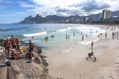 Men and women sit on a rock outcrop above Ipanema Beach at Rio de Janeiro in Brazil. Royalty Free Stock Images