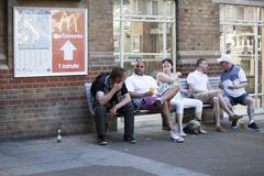 Men and women are sitting on a bench outside the station, talking animatedly Stock Photography