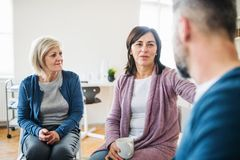 Men and women sitting in a circle during group therapy, supporting each other. Serious men and women sitting in a circle during group therapy, supporting each stock images