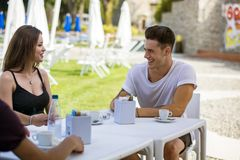 Men and women sitting at table drinking. Young handsome men and attractive women sitting at white plastic table drinking smoking talking and enjoying themselves Stock Images