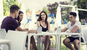 Men and women sitting at table drinking. Young handsome men and attractive women sitting at white plastic table drinking smoking talking and enjoying themselves Stock Photography