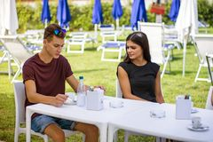 Men and women sitting at table drinking. Young handsome men and attractive women sitting at white plastic table drinking smoking talking and enjoying themselves Stock Photo