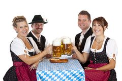 Men and women toast with Oktoberfest beer stein. Bavarian men and girls toast with Oktoberfest beer stein. Isolated on white background Royalty Free Stock Photo
