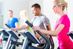 Men and women on treadmill in gym Stock Photos