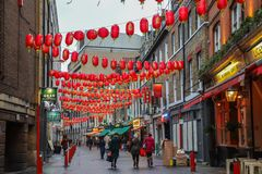 Men and women walking in streets in China Town in London stock photo