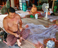Men and women weave a fishing net in the village Royalty Free Stock Photos