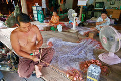 Men and women weave a fishing net in the village Stock Images