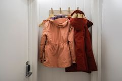 Men and women winter jacket hang at wall hook at house door stock photography
