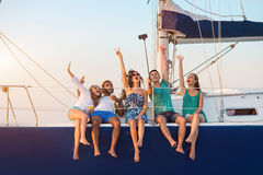 Men with women on yacht. Cheerful people with selfie stick. Men with women on yacht. Remember this moment. Happiness that comes from heart Stock Photography
