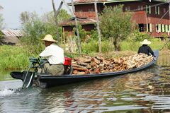 Men with wood on boat on Inle lake in Burma, Asia stock image