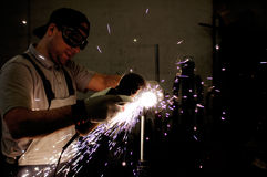 Men at work grinding steel. With a grinder and throwing off bright sparks around him while he works Royalty Free Stock Photos