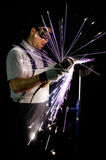 Men at work grinding steel. With a grinder and throwing off bright sparks around him while he works Stock Photo
