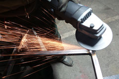 Men at work grinding steel. With a grinder in a metal fabrication factory and throwing off bright orange sparks around him while he works Stock Photography