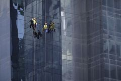 Men at work cleaning the facade of a skyscaper. Men at work hanging on ropes cleaning the glassy facade of a skyscaper royalty free stock photo