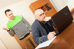 Men at work on laptop. Two adult males at laptop at table stock photography