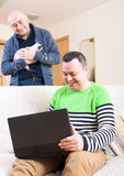 Men at work on laptop. Two men with black laptop at home stock images