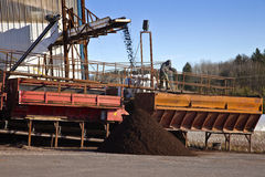 Men at work processing compost for agriculture. Stock Image