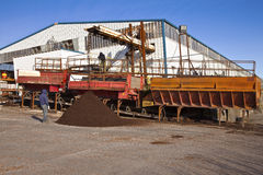 Men at work processing compost for agriculture. Stock Photos