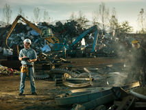 Men at work in recycling center. Caucasian engineer standing at scrap metal recycling site, inspecting work Stock Images
