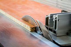 Men at work sawing wood. Circular saw. A machine which saws wood, particle Board and fiberboard. Royalty Free Stock Photo