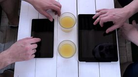Two men are typing on a tablet in a cafe. View from above. Men work with tablets in a cafe stock footage